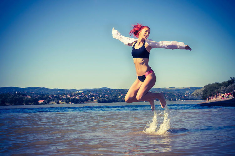 Full length of woman with arms raised in sea against clear sky