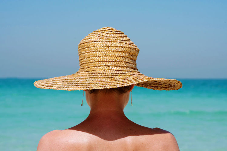 View from behind woman at the beach wearing straw hat against the sea
