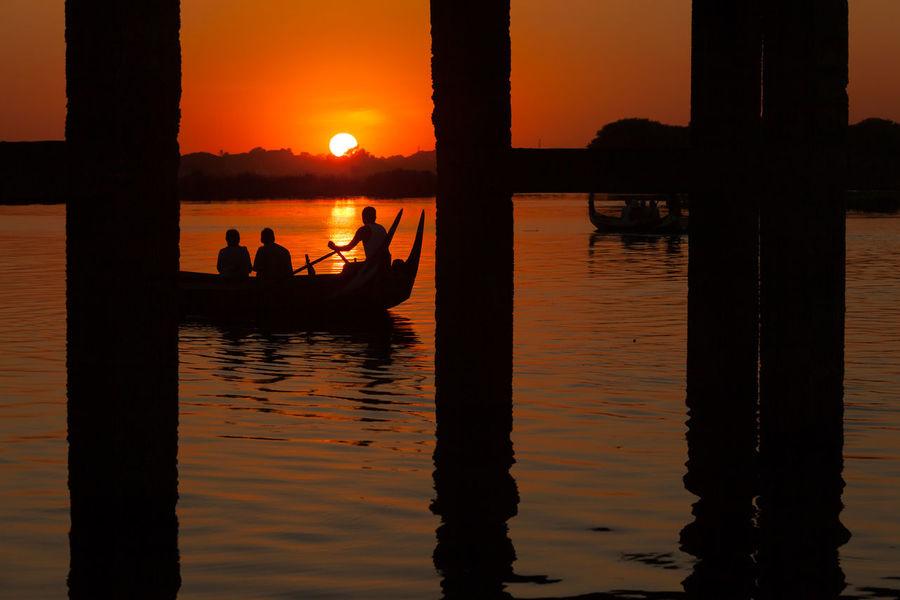 Silhouetted people on boat under U-Bein bridge at sunset, Amarapura, Mandalay, Myanmar Boat Bridge Burma Evening Myanmar River River View Sampan Silhouette South East Asia Sun Sunlight Sunset Tourist Ubeinbridge