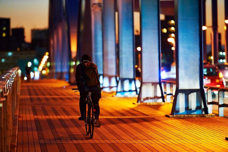 Rear View Of Man Riding Bicycle On Bridge At Night