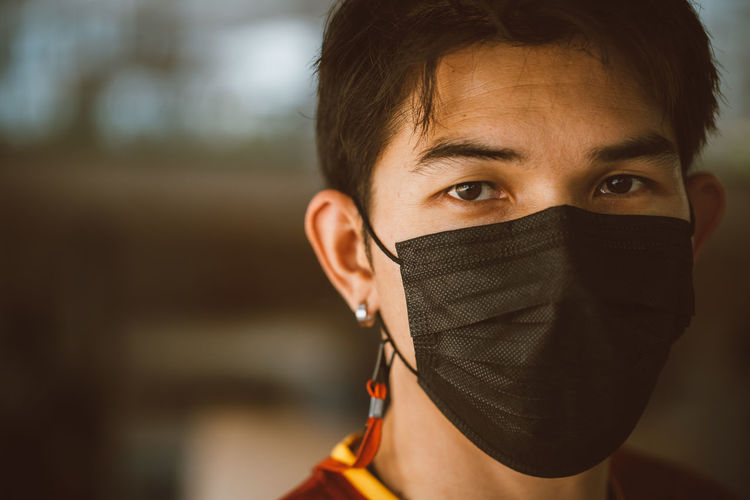 Young man wearing a black mask to protect against the virus.