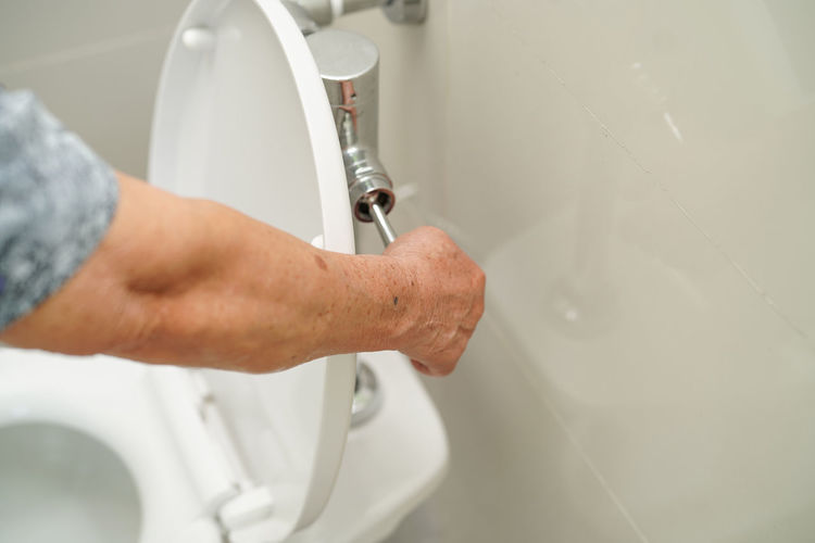Cropped hand of man flushing toilet in bathroom