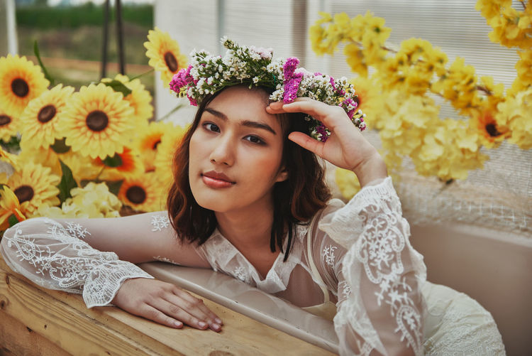 Portrait of beautiful young woman sitting by potted plant