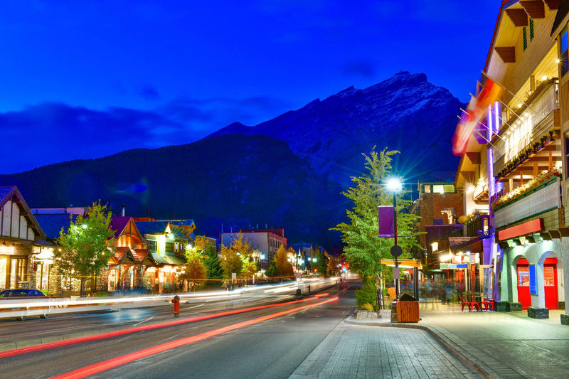 Street view of famous Banff Avenue at twilight time. Banff is a resort town and one of Canada's most popular tourist destinations. Illuminated City Night Architecture Building Exterior Mountain Street Road Long Exposure Transportation Light Trail Motion Built Structure Sky Building Mountain Range Dusk Blurred Motion Mode Of Transportation Speed No People Light Outdoors Cityscape Banff  Twilight Town Canada Avenue