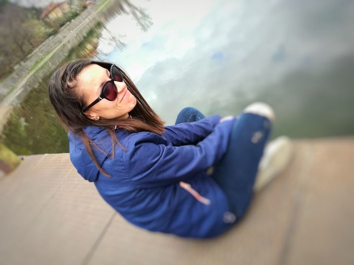 High angle view of smiling young woman in sunglasses sitting on jetty over lake