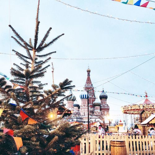 Christmas tree by orthodox church against sky during winter