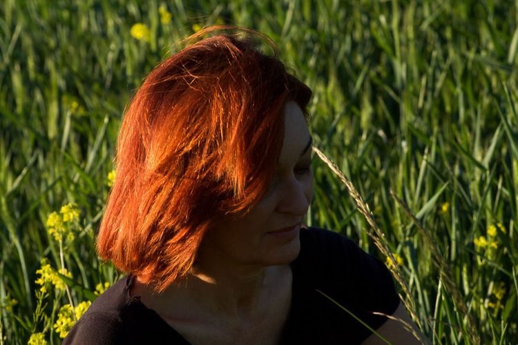 Close-up of woman by grass on field