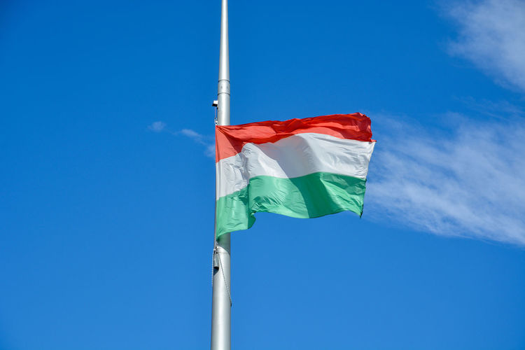 Low angle view of hungarian flag waving against clear blue sky