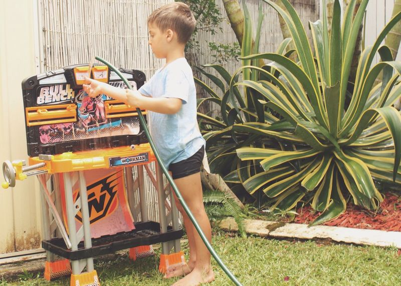 Young boy concentrating while washing his toy workbench in the garden Child Family Watering Chores Workbench Toy Garden Childhood Hose Washing Cleaning Showcase March Backyard Casual Clothing The Portraitist - 2016 EyeEm Awards Home Is Where The Art Is