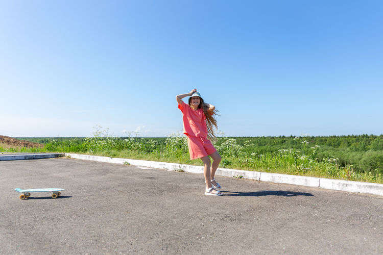 Woman standing on road against clear blue sky