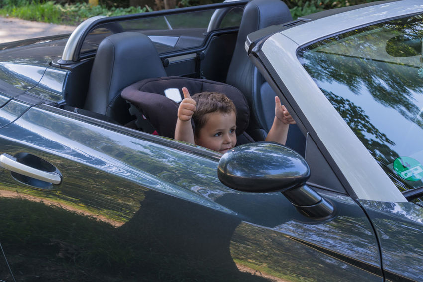 Happy laughing child in a convertible sits in the car child seat and shows the thumbs up. Boys Car Child Childhood Day Innocence Land Vehicle Leisure Activity Lifestyles Males  Men Mode Of Transportation Motor Vehicle One Person Outdoors Portrait Real People Transportation