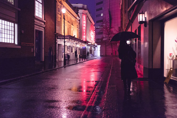 Woman walking on road in city at night