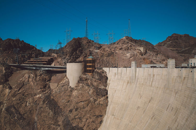 Hoover dam by rocky mountain against sky
