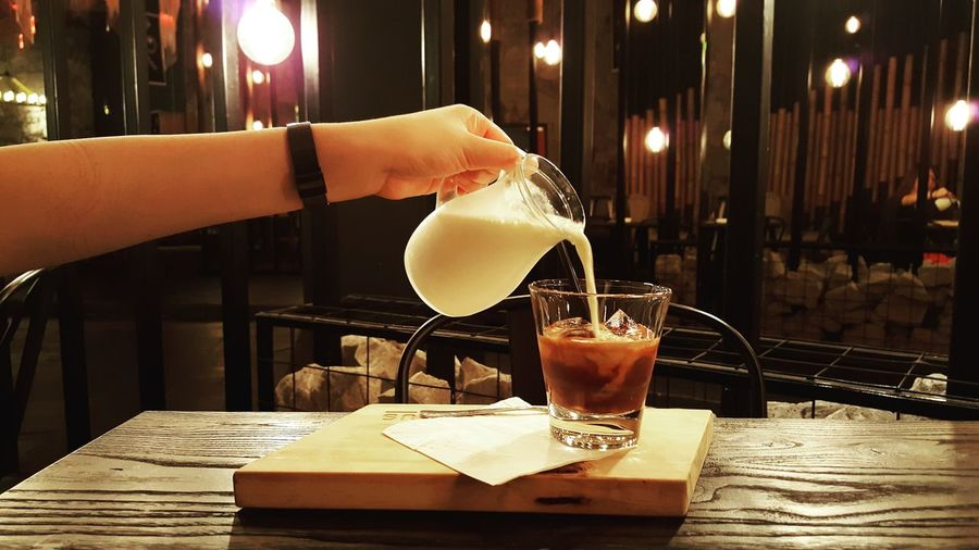 Close-up of person pouring milk over coffee