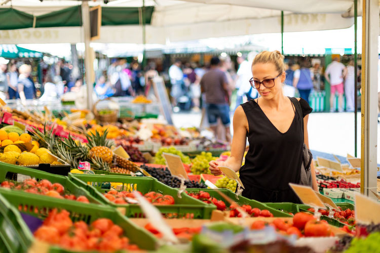 Mid adult woman standing at market stall