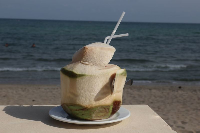Close-up of coconut water with straw in plate on table at beach