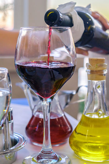 Cooking Oil Dinner Mediterranean Culture Mediterranean Food Pouring Quality Time Red Red Wine Alcohol Alcoholic Drink Bottle Close-up Drink Fine Dining Focus On Foreground Food And Drink Glass - Material Human Hand Indoors  Olive Oil Restaurant Table Vinegar Wine Wineglass