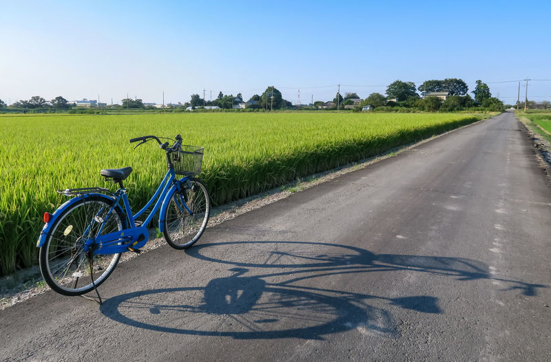 Bicycle parked by road on field against clear blue sky