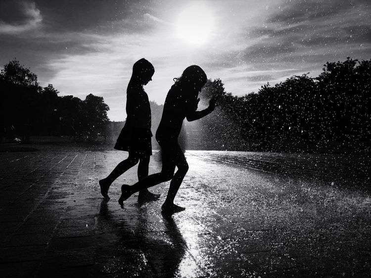 A rainy day in Berlin Two People Leisure Activity Silhouette Togetherness Playing Wet Water Real People Fun Friendship Full Length Motion Enjoyment Lifestyles Bonding Outdoors Women Men Sky Boys Blackandwhite Photography Black And White Kids Being Kids Blackandwhite Black & White