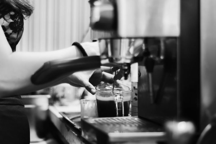 Barista making fresh coffee for service to customer