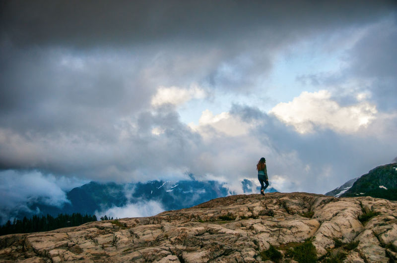 Low angle view of woman walking on rocky hill against cloudy sky