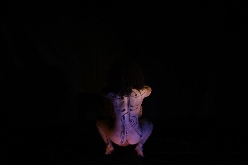 Rear view of naked woman crouching against black background