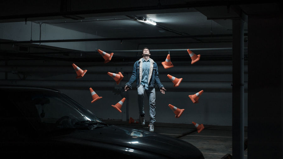 Man levitating by traffic cone s and car in parking lot at night