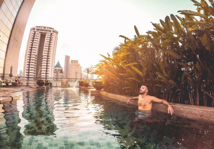 Full length of shirtless man sitting in swimming pool against sky