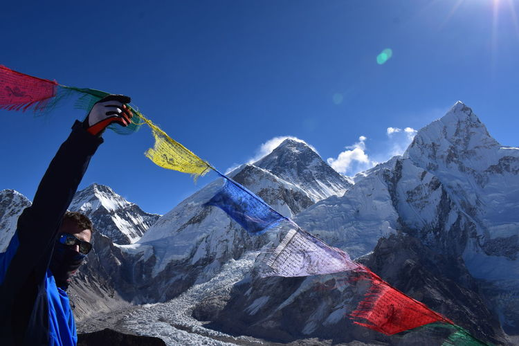 Man touching prayer flag during winter