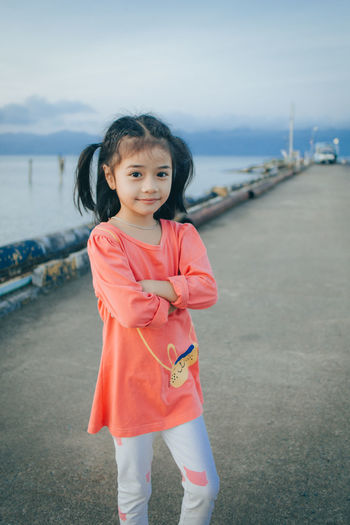 Portrait of cute girl standing at shore