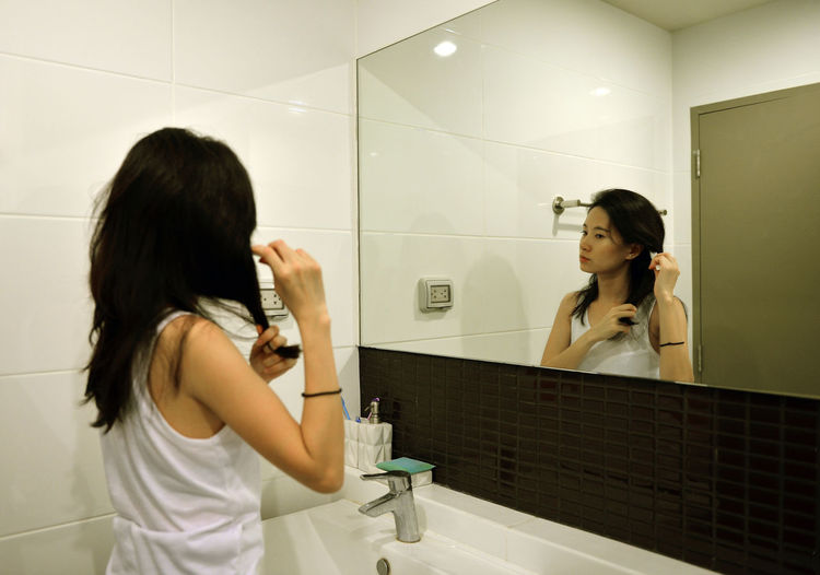Woman making hairstyle while reflecting of mirror in bathroom