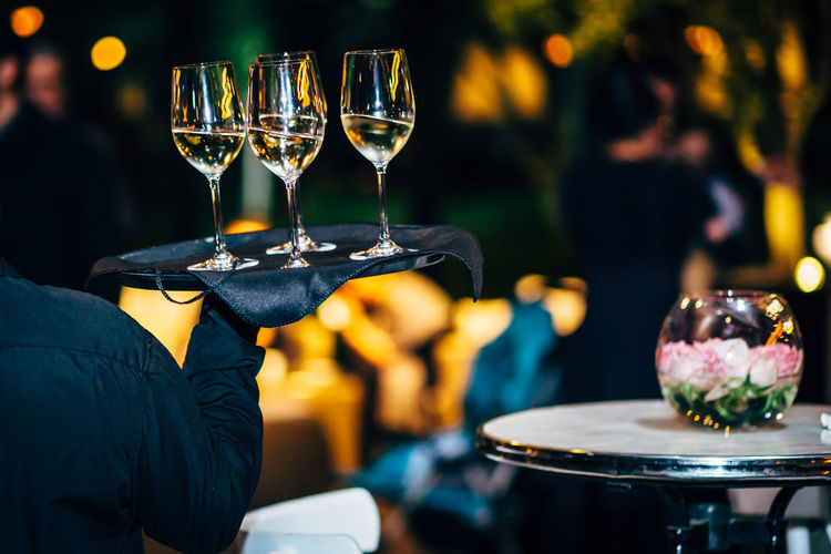 Rear view of waiter carrying champagne at restaurant