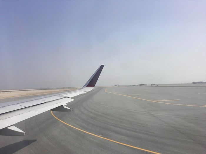 Cropped Image Of Airplane On Runway Against Sky