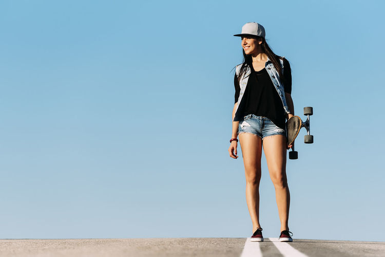 Woman holding skateboard standing on road against clear blue sky