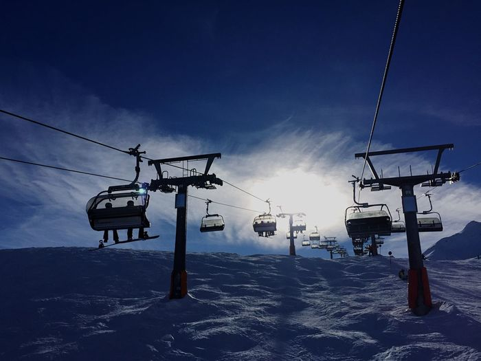 Low angle view of ski lift against sky during winter