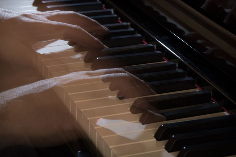 Digital composite image of hands playing piano