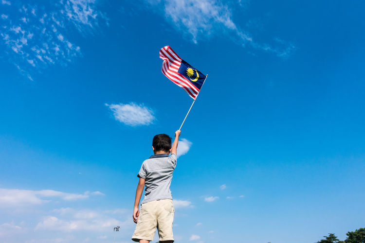 Low angle view of boy holding flag while standing against blue sky