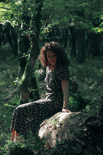 Full length of woman sitting on tree in forest