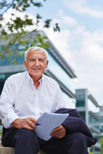 Portrait Of Senior Businessman Sitting In City