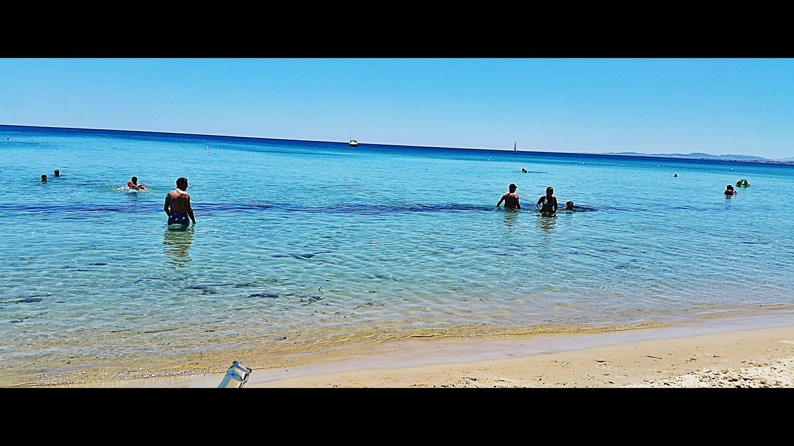 sea, water, beach, horizon over water, leisure activity, lifestyles, shore, vacations, enjoyment, scenics, beauty in nature, medium group of people, blue, nature, wave, mixed age range, sky, tranquil scene, tourist, summer, tranquility, coastline, tourism, outdoors, ocean