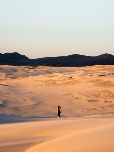 A lone photographer walks the windswept dunes that make up Stockton Sand Dunes, Australia. The dark patches that can be seen are wet patches where the wind has blown the top layer of dry, soft sand off, leaving the marble texture to show through. Australia Australian Landscape Beautiful Olympus Adventure adventures in the city Beauty In Nature Clear Sky Em1mk2 Land Leisure Activity Lifestyles Mountain One Person Real People Sky Sunset Tranquil Scene Tranquility Week On Eyeem The Great Outdoors - 2018 EyeEm Awards The Traveler - 2018 EyeEm Awards A New Beginning A New Perspective On Life Capture Tomorrow