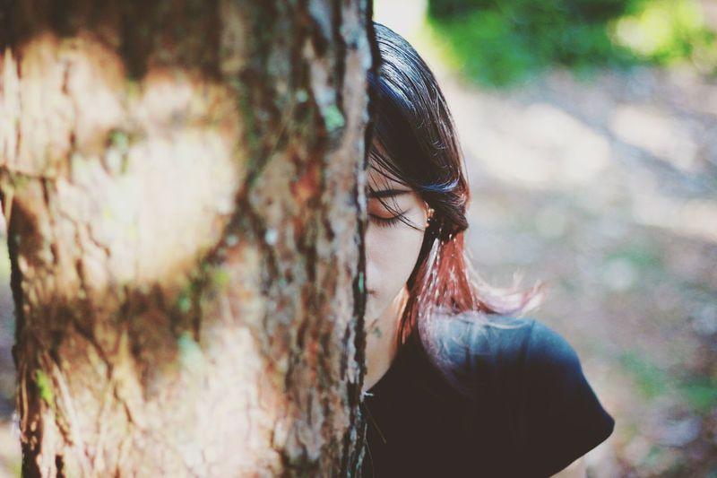 Close-Up Of Woman Behind Tree
