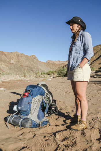 Female hiker standing on sandy terrain next to her backpack Adventure Backpack Beauty In Nature Desert Exploration Explore Hat Hike Hiker Hiking Leisure Activity Mountain Mountain Range Nature Nature Outdoor Outdoor Photography Outdoors Rugged Sand Scenics Summer Wild Wilderness Young Women