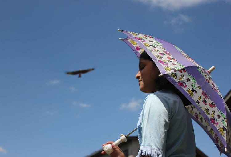 Low angle view of girl holding umbrella against blue sky