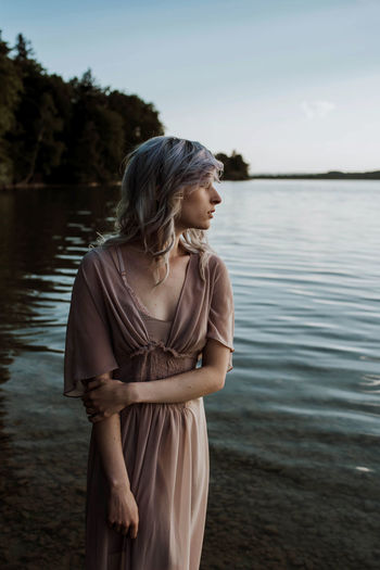 Young Woman Standing By Lake