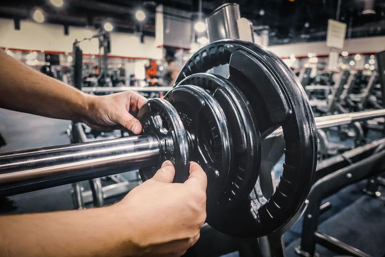 Close-Up Of Man Putting Weights In Barbell At Gym