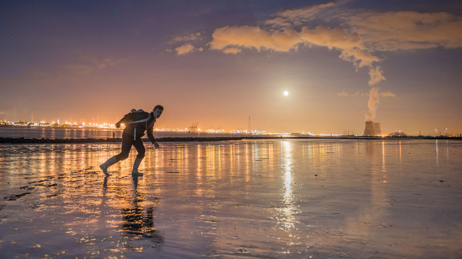 Moon Over Cityscape And Man Walking On Water