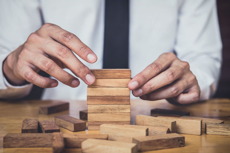 Midsection of businessman stacking wooden toy blocks at desk