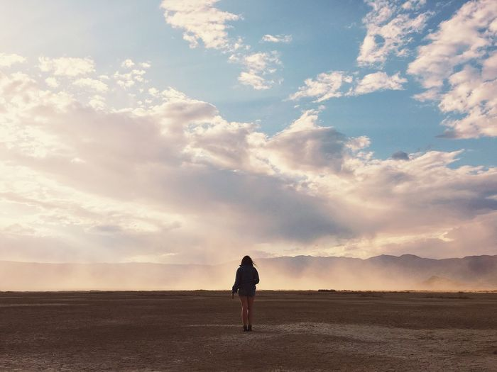 Woman standing on landscape against sky during sunset
