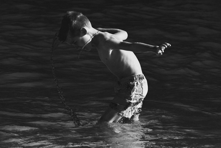 Side view of shirtless boy splashing water in sea